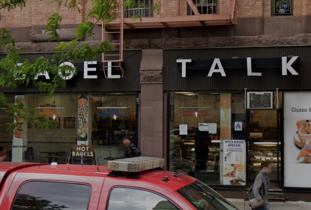 A bagel shop shaded by trees with a red truck in front.
