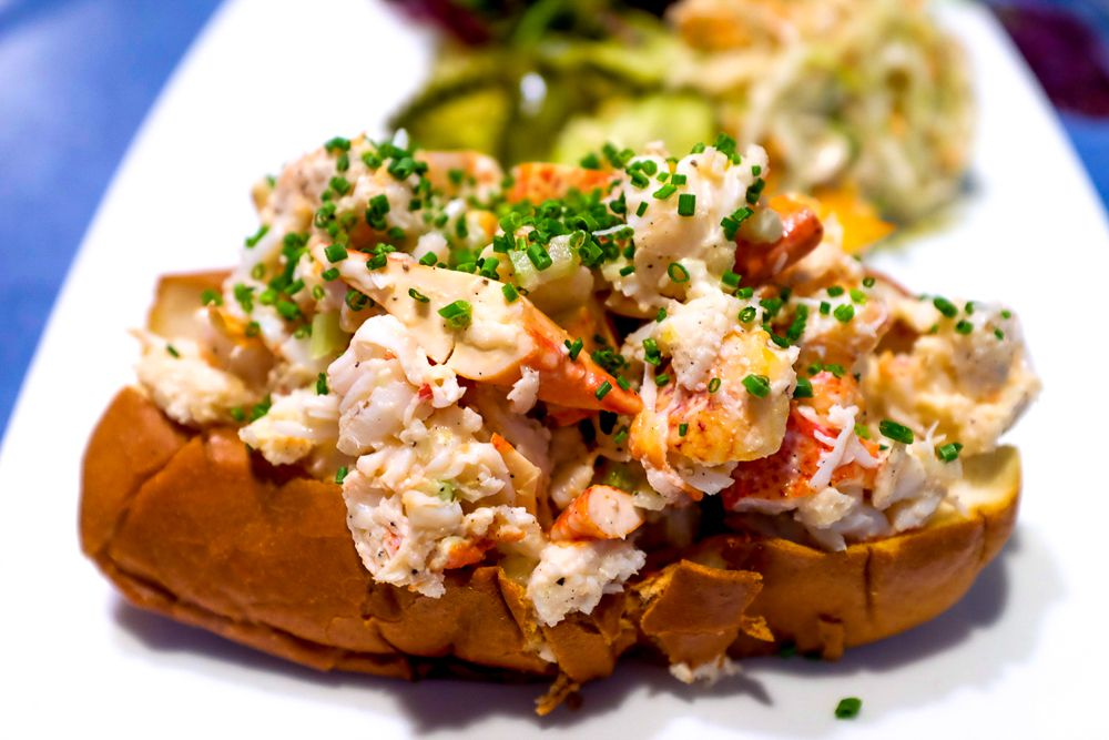 The lobster roll at B&G Oysters sits atop a white plate, and is topped with shockingly green minced chives.