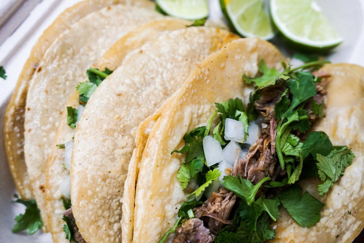A close-up view of three tacos with roasted, fork tender, juicy lamb meat
