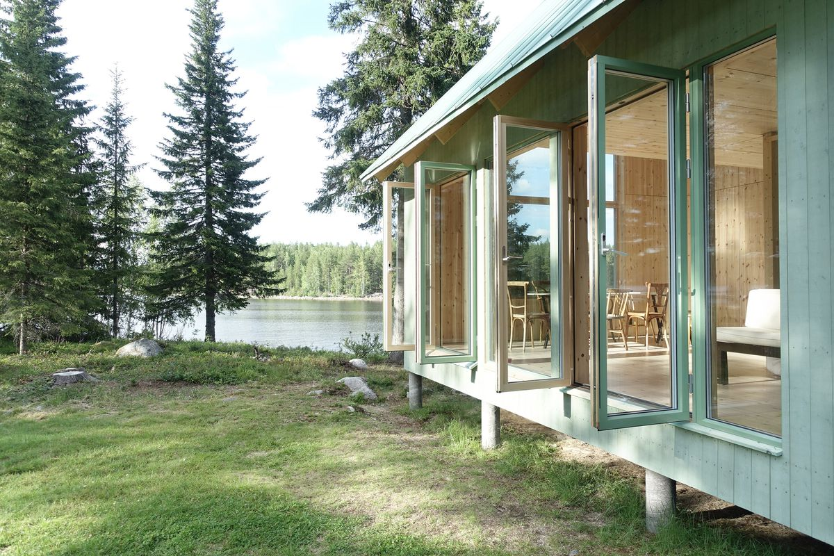 A side view of a mint green cabin on stilts. Glass doors open to reveal all pale wood interiors. Evergreen trees surround a lake in the background.
