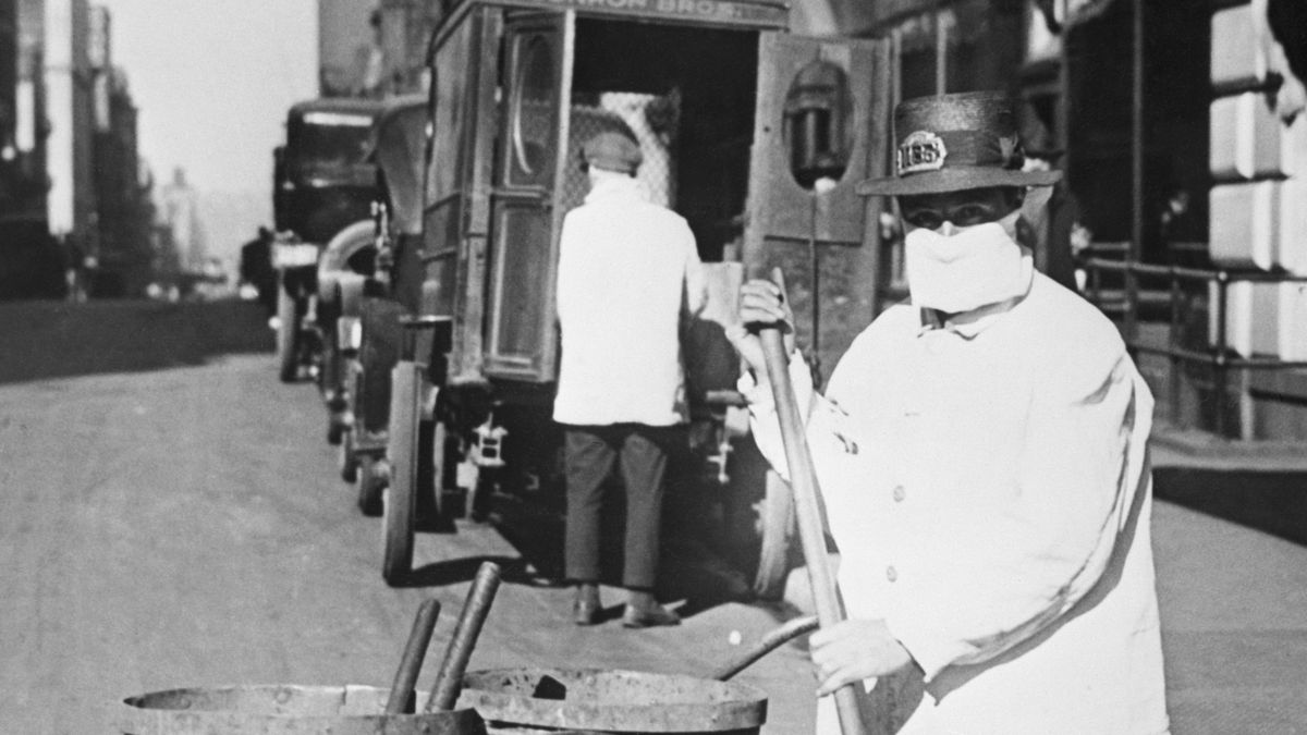 A city worker in New York City in 1918 cleaning the street wearing protective gear to fight the spread of influenza.