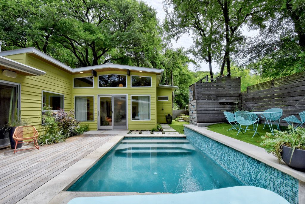 A backyard area shows an exterior view of a green house and a pool.