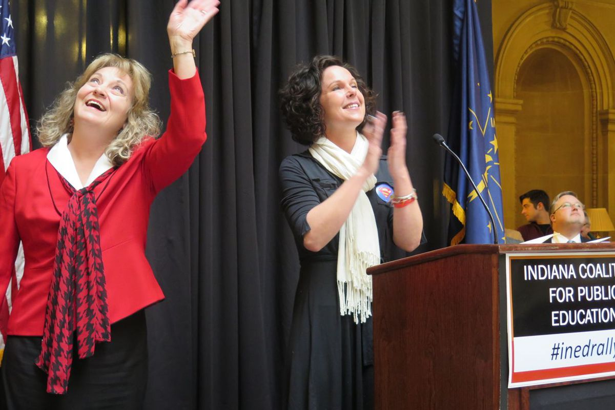 State superintendent Glenda Ritz waves to supporters on the second level of the Statehouse as she joins Marisa Graham, vice president of the Anderson teachers union, at the podium at Monday's rally.