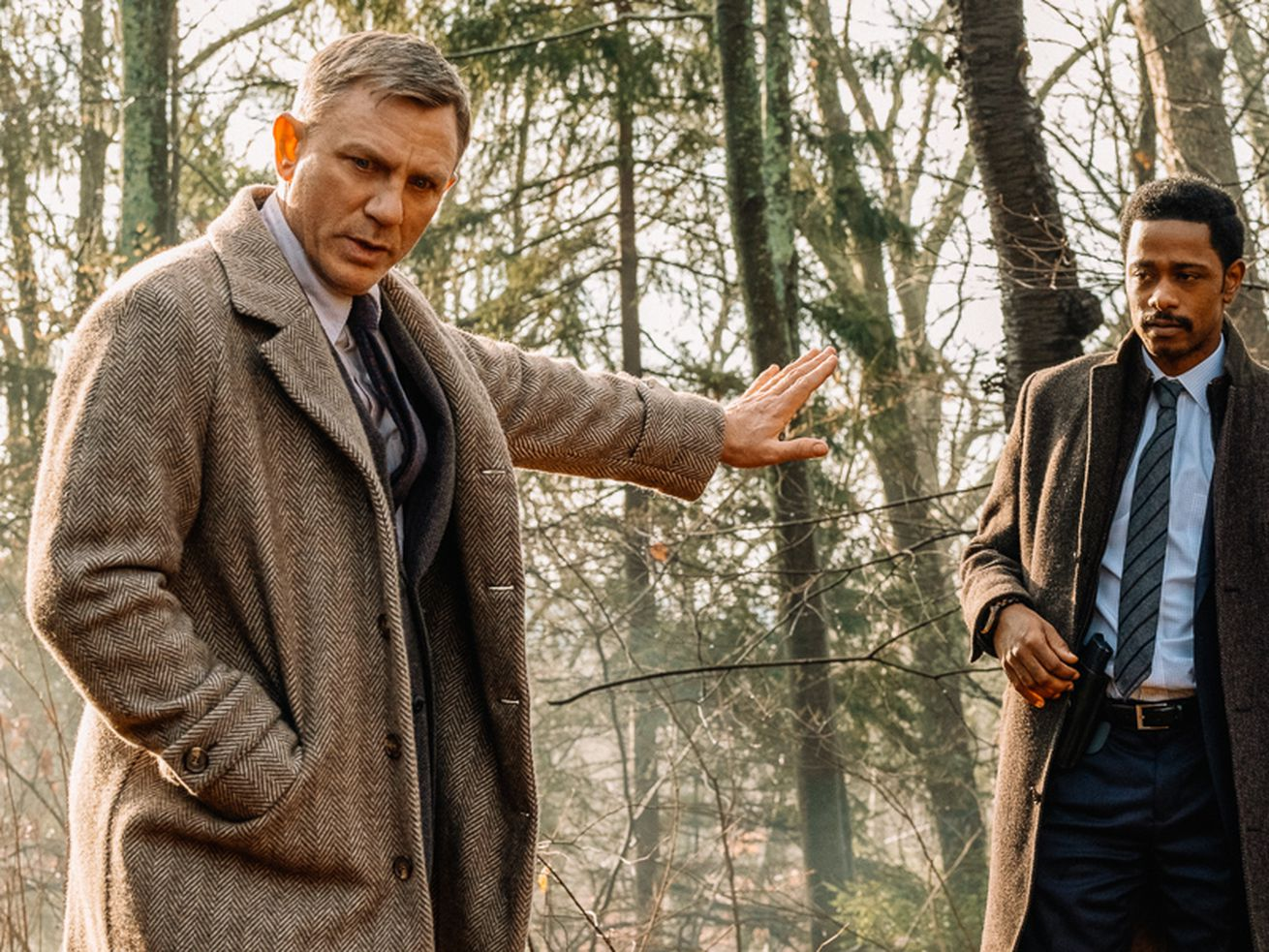 """Daniel Craig, Lakeith Stanfield, and Noah Segan stand in the woods in the movie """"Knives Out."""""""