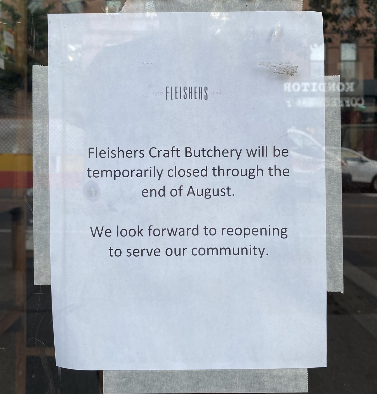 """A sign posted to the front door of a glass door reads, """"Fleishers Craft Butchery will be temporarily closed through the end of August. We look forward to reopening to serve our community."""""""