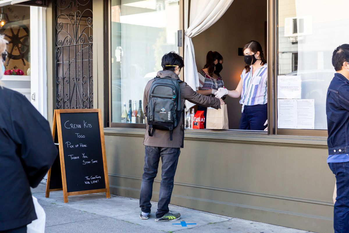 A customer picks up a meal kit at Atelier Crenn