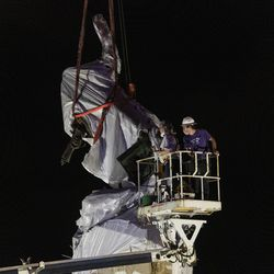 City crews cut away part of the tarp that's covering the Christopher Columbus Statue in Grant Park as the statue is being removed, Friday, July 24, 2020.