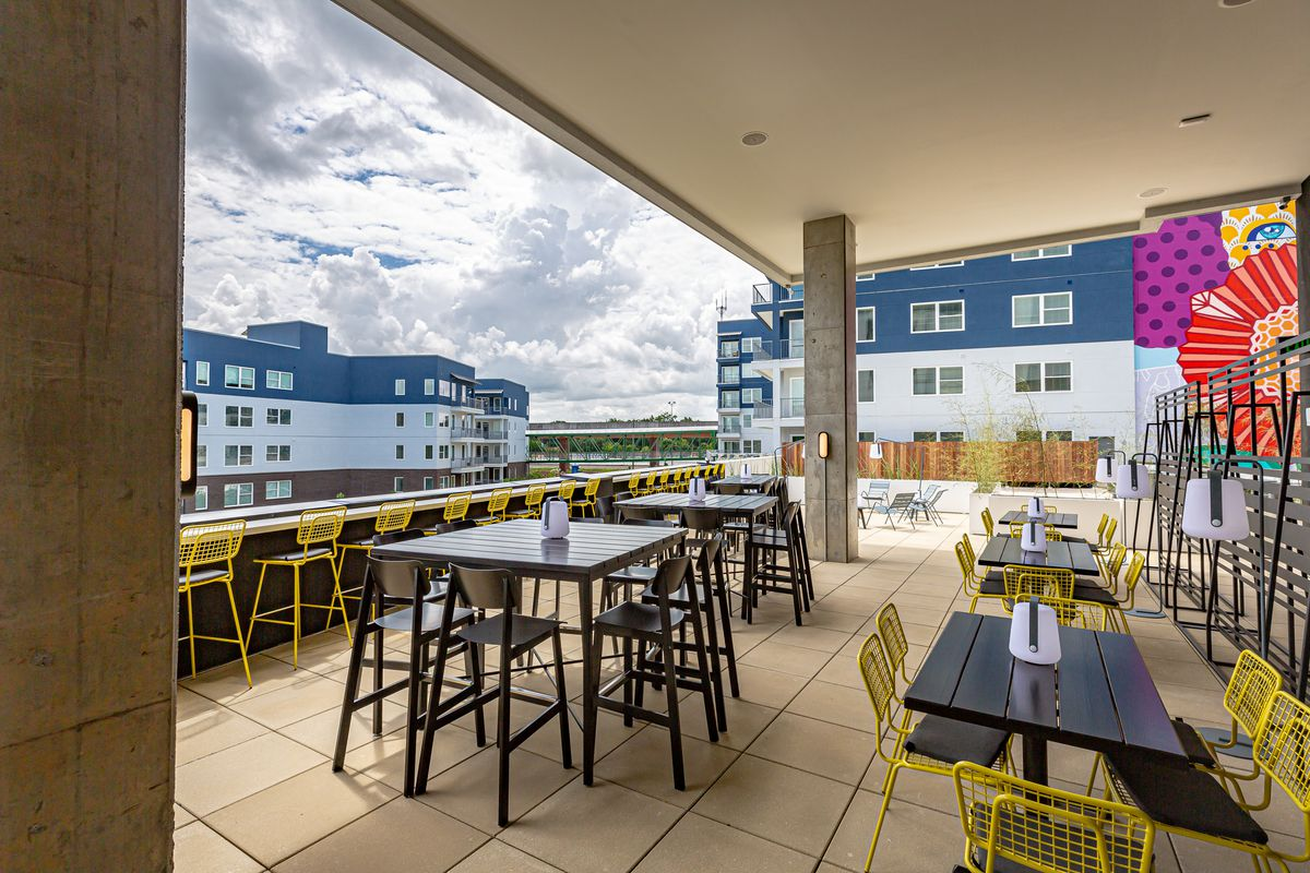 Cold Beer rooftop patio looking toward Dekalb Avenue with low and high top table seating