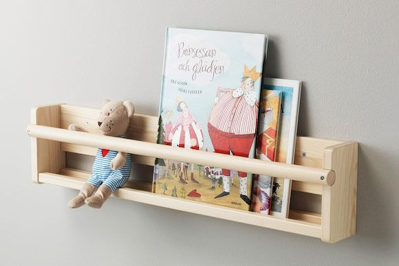 Pale wood shelving with books and stuffed animals.