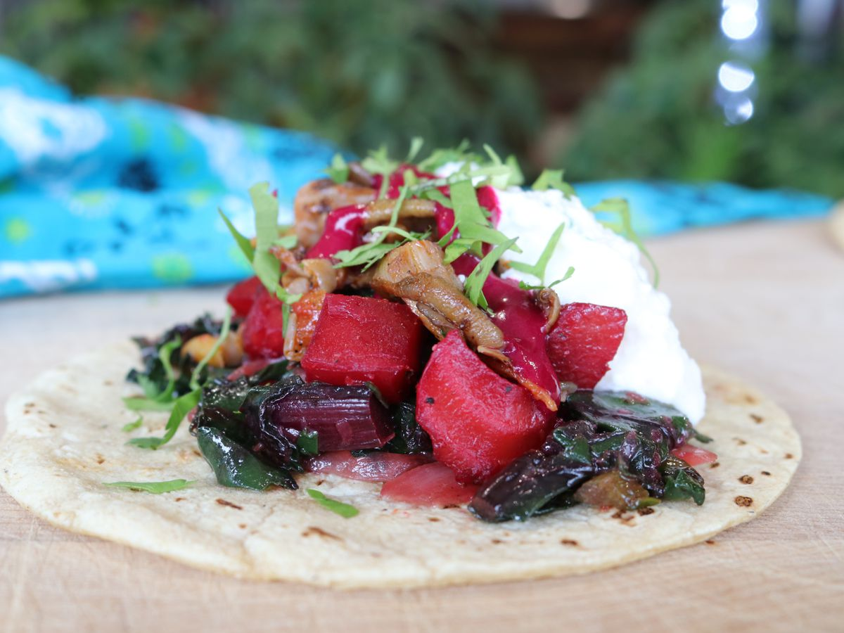 A taco loaded with bright cubed beets, cooked mushrooms, and crema