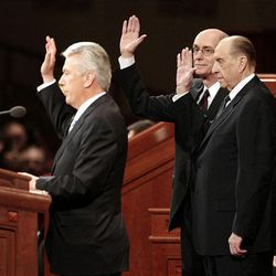 President Dieter F. Uchtdorf, left, President Henry B. Eyring and President Thomas S. Monson raise their hands to sustain President Monson as president of The Church of Jesus Christ of Latter-day Saints. Saturday morning's solemn assembly was held during the 178th Annual General Conference at the Conference Center.