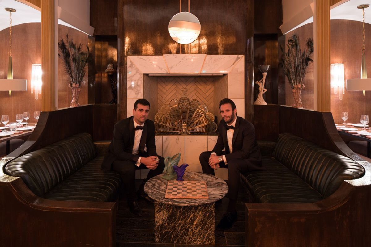Two men in tuxedos sit, leaning towards a central fireplace.