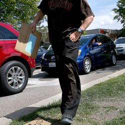 Jessie Cone stuffs a dollar bill in his pocket while panhandling on 400 South in Salt Lake City on Friday, May 1, 2015. A Utah Policy poll finds 2/3 of Salt Lake City residents think panhandling should be illegal. Cone believes that there would be a rise in shoplifting if panhandling becomes fully illegal.