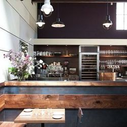 The open kitchen includes a wood-fired rotisserie, and a 16-foot chef's counter where plating wraps up.