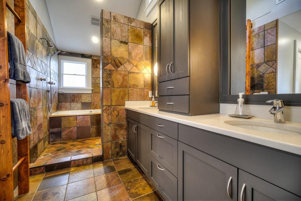 A master bathroom with brown and pinkish tile.