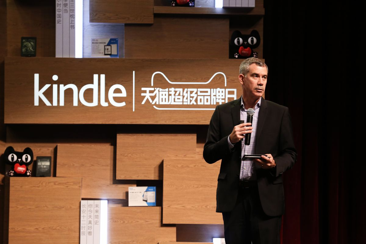 Amazon Kindle exec Bruce Aitken stands in front of a Kindle sign in both English at Chinese at an Amazon-Alibaba press event in China.