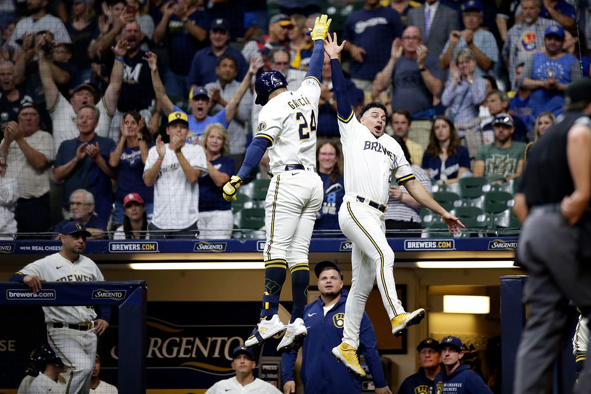 Willy Adames #27 congratulates Avisail Garcia #24 of the Milwaukee Brewers after hitting a solo home run in the second inning against the St. Louis Cardinals at American Family Field on September 20, 2021 in Milwaukee, Wisconsin.