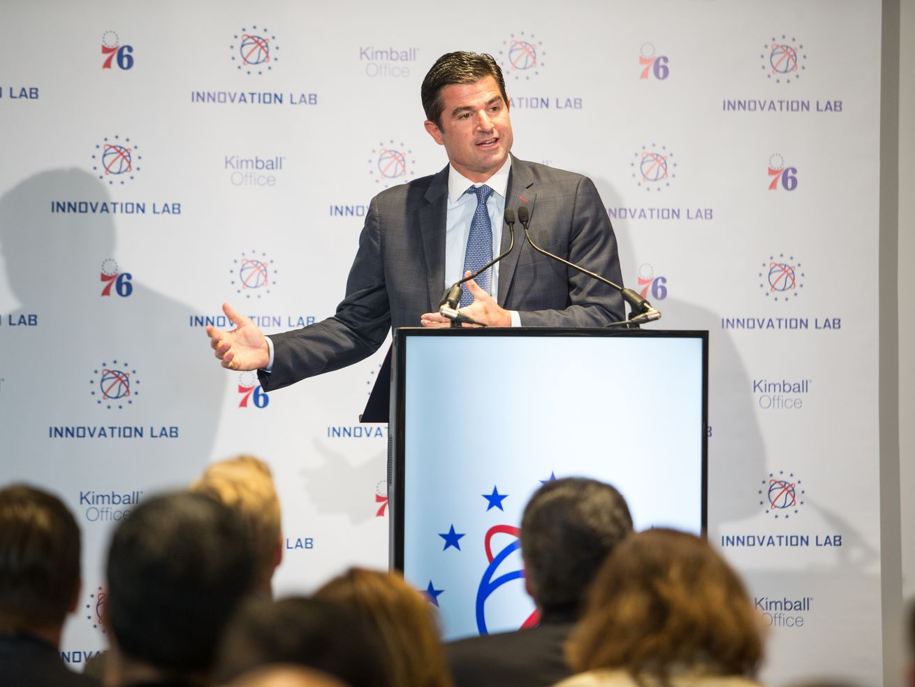Philadelphia 76ers' CEO Scott O'Neil stands at a podium to speak at an event.