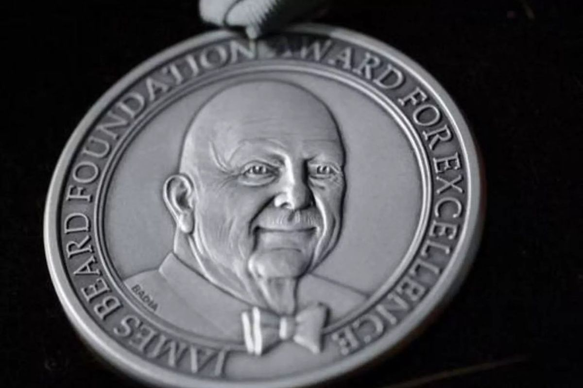 "A silver James Beard Awards medal featuring James Beard's face at center and the words ""James Beard Foundation Award for Excellence"" along the border."