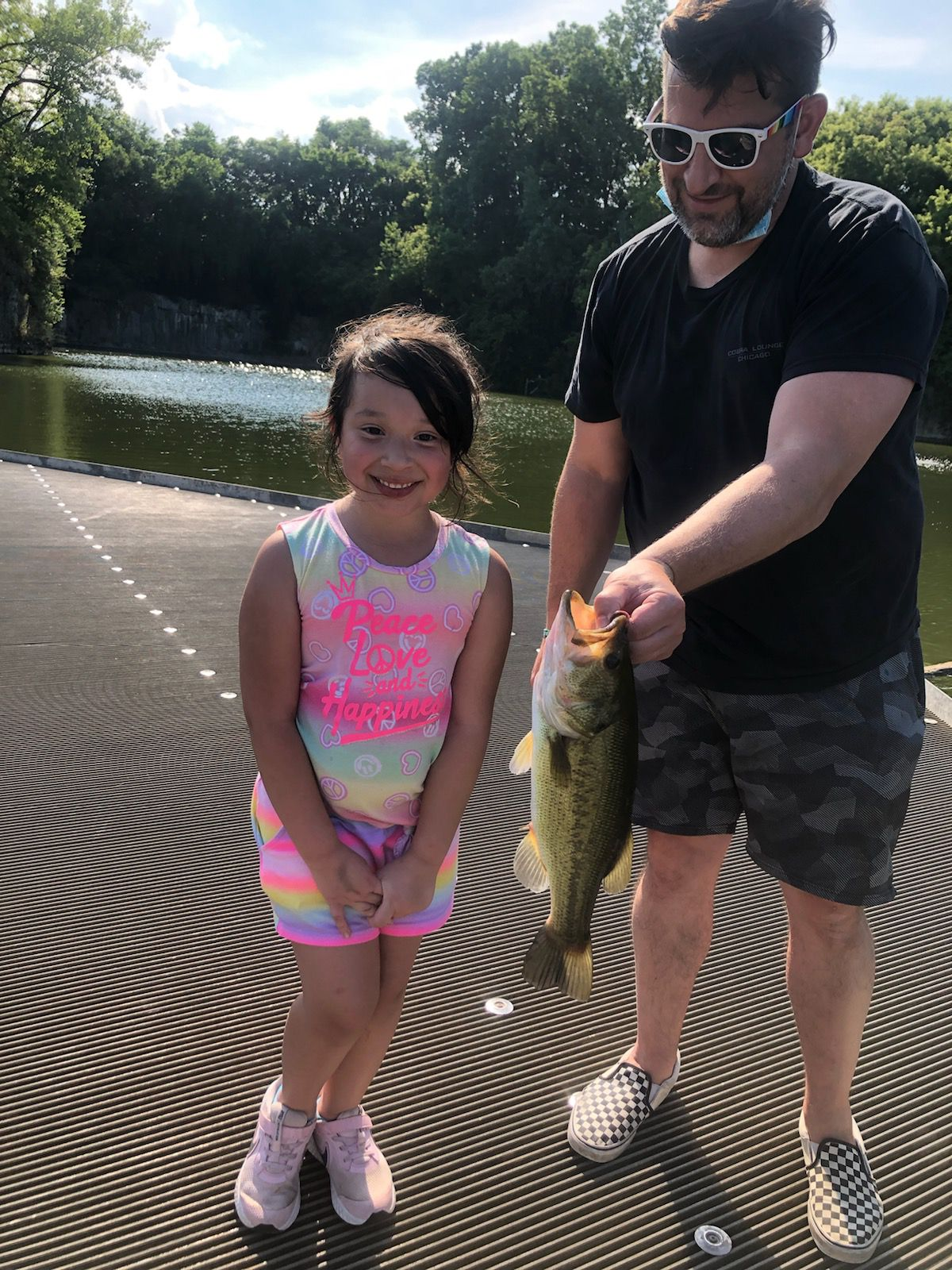 Valeria Vazquez holds a largemouth bass, with help from David Czuprynski, she caught on an ice rod at Palmisano Park. Photo provided
