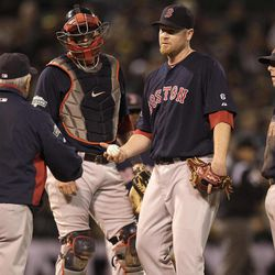 Boston Red Sox pitcher Aaron Cook, second from right, hands the ball to manager Bobby Valentine as he is removed from the baseball game against the Oakland Athletics in the third inning Friday, Aug. 31, 2012, in Oakland, Calif.