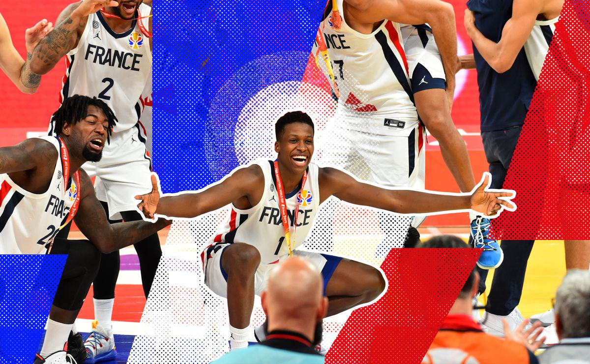 Frank Ntilikina posing with his arms out wide and smiling in celebration while wearing his World Cup bronze medal, surrounded by Team France teammates.