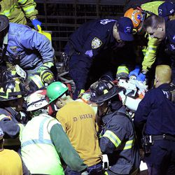 Police and fireman remove an injured person from the site of a crane collapse where construction is going on for the 7 line subway extension Tuesday, April 3, 2012, in New York. Fire officials say a crane collapse at a Manhattan construction site has injured two people.