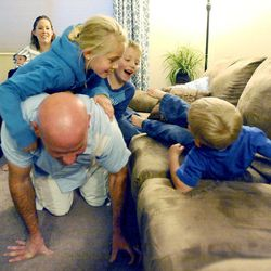 Kelly Burton flips 3-year-old Logan, right, onto the couch as 8-year-old Mykenzie and 6-year-old Porter jump on his back and mom Mary looks on with 2-month-old Raiger at the family's home Sept. 25.