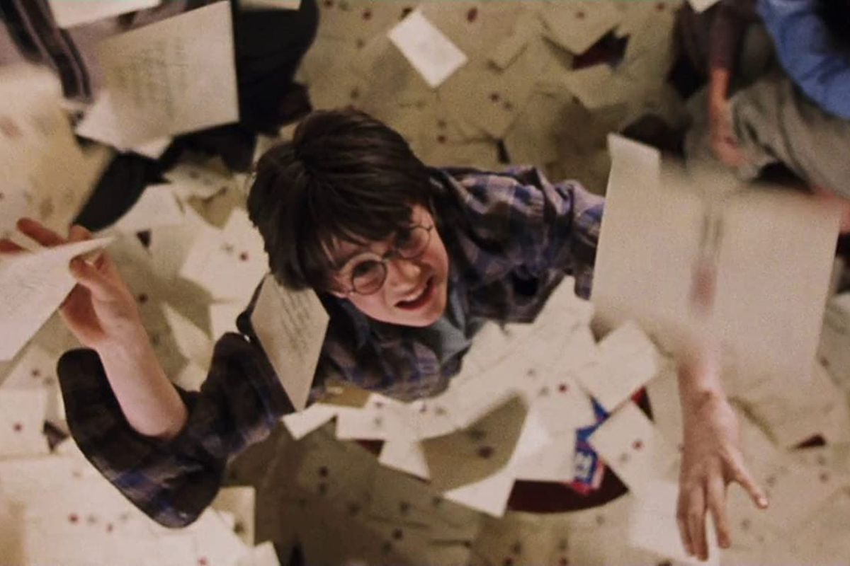 Harry (Daniel Radcliffe) grabs at letters falling from the ceiling