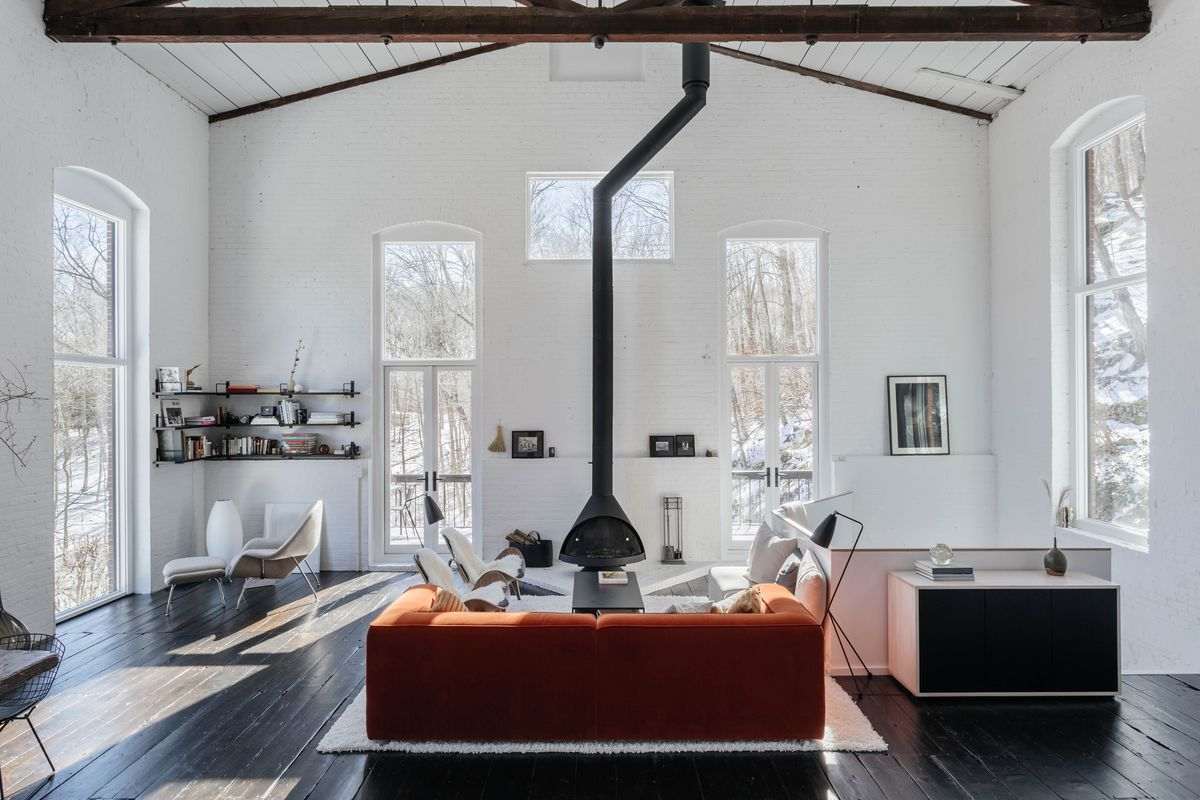 Living room with a rust-colored sofa, white walls, and black wood burning stove in the center.