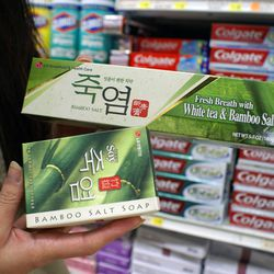 """↑ We stroll over to the toothpaste aisle, where Yara stocks up on bamboo salt toothpaste and soap. """"It's like tea tree oil, but [Koreans] usually ingest it to help fight disease. They'll also take roasted bamboo salts and put it into scrubs. When you go t"""