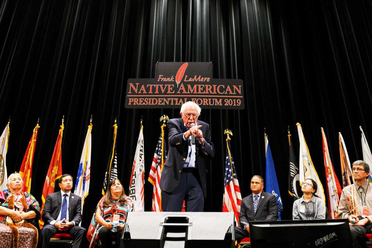 Presidential candidate Senator Bernie Sanders stands onstage speaking into a microphone and pointing at the audience. Also onstage are seated representatives of Native peoples and the flags of many tribes.