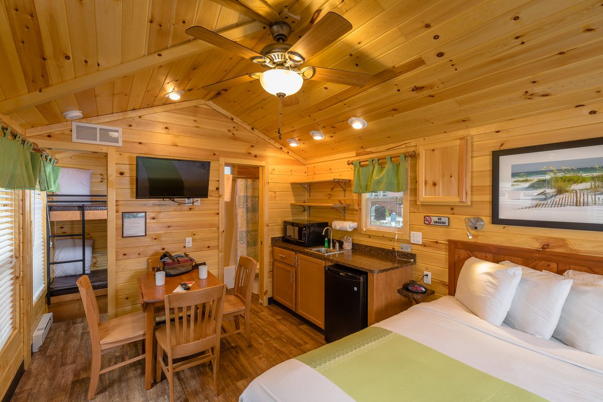 A cabin interior includes a white bed, small wooden table for four, TV on the wall, and galley kitchen with a window above it.