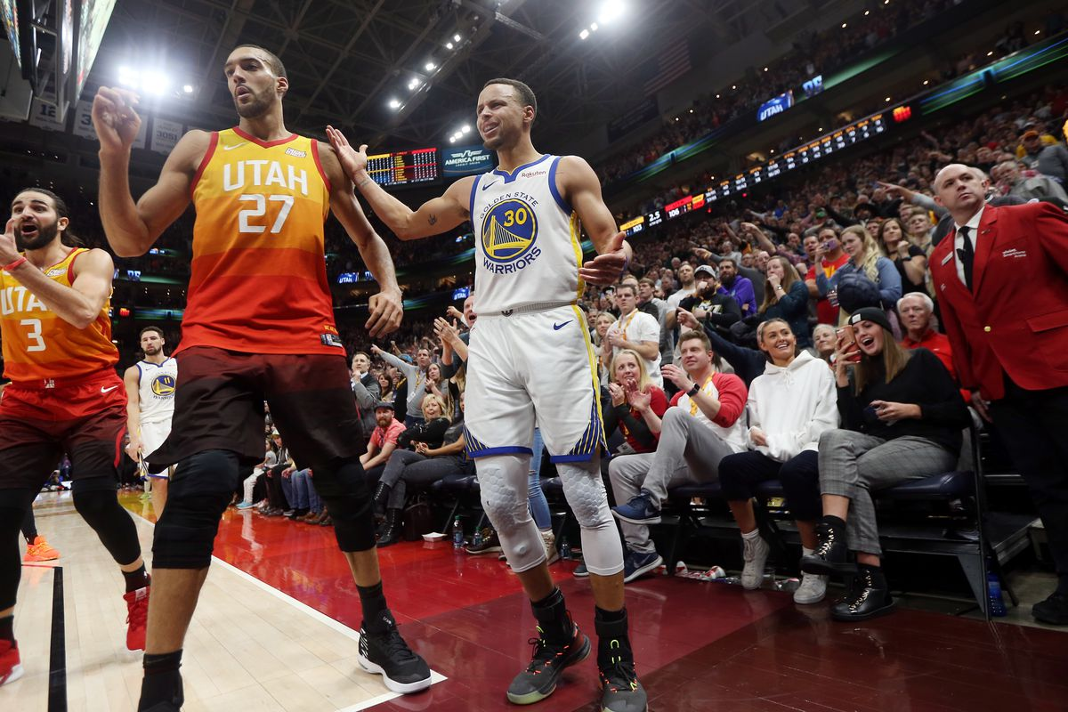 Utah Jazz guard Ricky Rubio (3) Utah Jazz center Rudy Gobert (27) Golden State Warriors guard Stephen Curry (30) argue the call as the Utah Jazz and the Golden State Warriors play an NBA basketball game at Vivint Smart Home Arena in Salt Lake City on Wedn