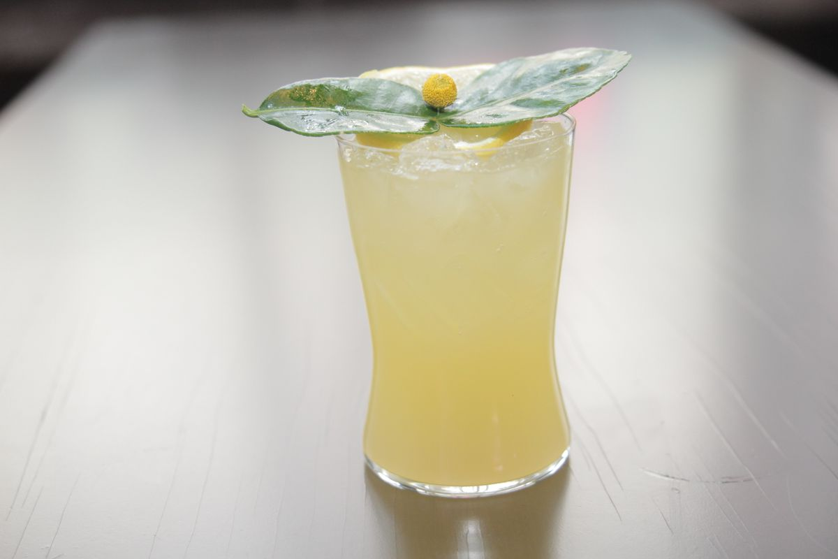 A yellow cocktail with mint leaf on top