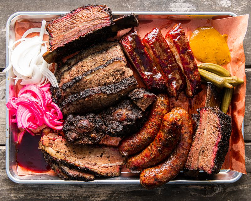 A tray of barbecued meats — sliced brisket, ribs, links, and an on-the-bone beef rib — with a small pile of pink pickled onions to the side