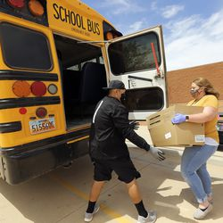 Thurman Cly, school interventionist, and Amy Reeve, fifth grade teacher, load a box of food into a school bus to deliver to students while schools are closed due to COVID-19, outside of Tse'bii'nidzisgai Elementary School in Oljato-Monument Valley, San Juan County, on Thursday, April 30, 2020. Navajo Nation has one of the highest per capita COVID-19 infection rates in the country.