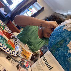 Ayden gets his hands dirty coloring a piñata.