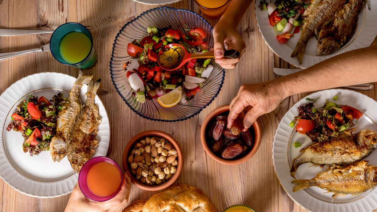 An overhead shot of an Iftar meal on a wooden dining table. Hands reach in from the top, right, and bottom to grab dates, mix a salad, and hold a cup.