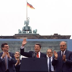 U.S. President Ronald Reagan acknowledges the applause after speaking to an audience in front of the Brandenburg Gate in Berlin on Friday, June 12, 1987.