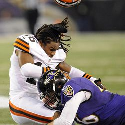 Baltimore Ravens long snapper Morgan Cox tackles Cleveland Browns wide receiver Josh Cribbs (16) as Cribbs' helmet is dislodged from a hit by another player during the first half of an NFL football game in Baltimore, Thursday, Sept. 27, 2012.