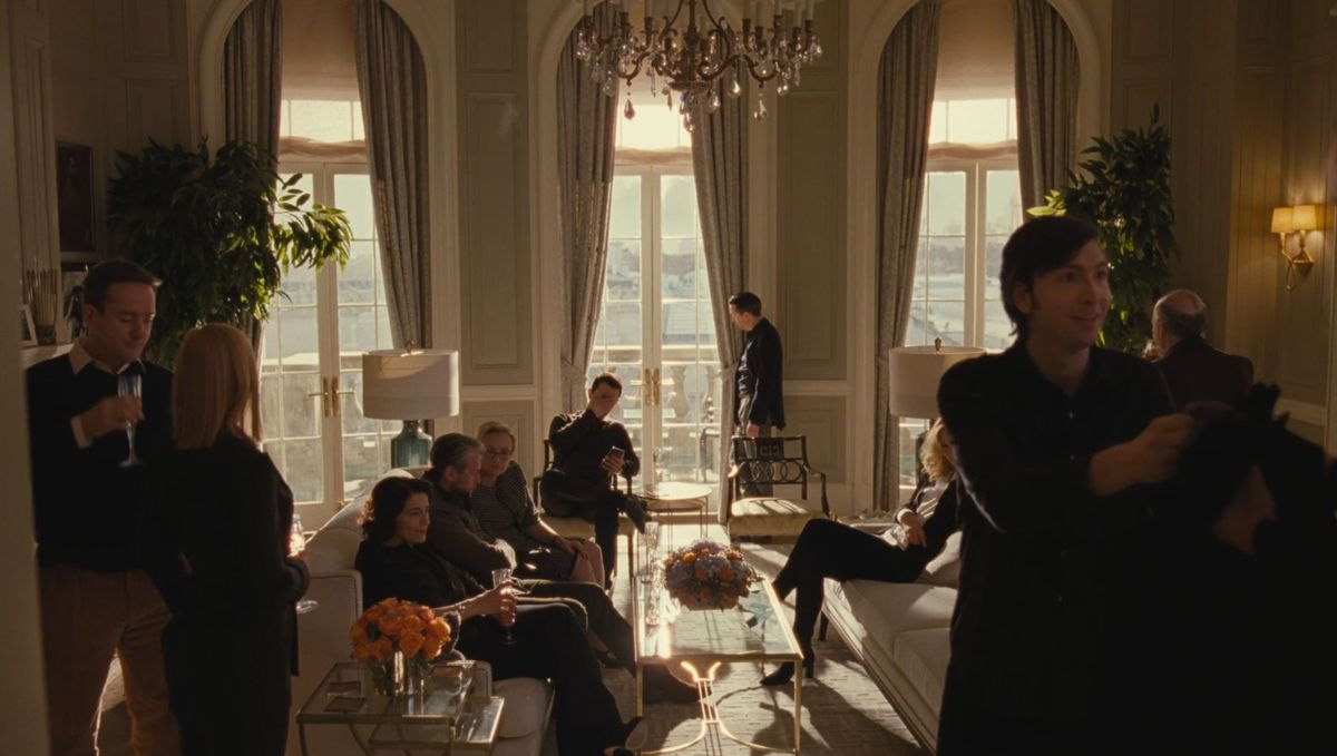 A group of people are sitting in a large living room in the HBO show Succession. There are tables, couches, lamps, plants, and a large chandelier hanging from the ceiling. There are floor to ceiling windows with drapery.