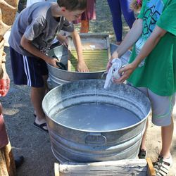 A group of children washing laundry on a washboard similar to one the pioneers would have used in July 2014. In addition to washing laundry, Moyle Park's pioneer activities include making candles, churning butter and dancing.