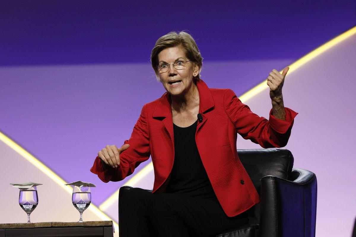 Sen. Elizabeth Warren seated onstage speaking to an audience.