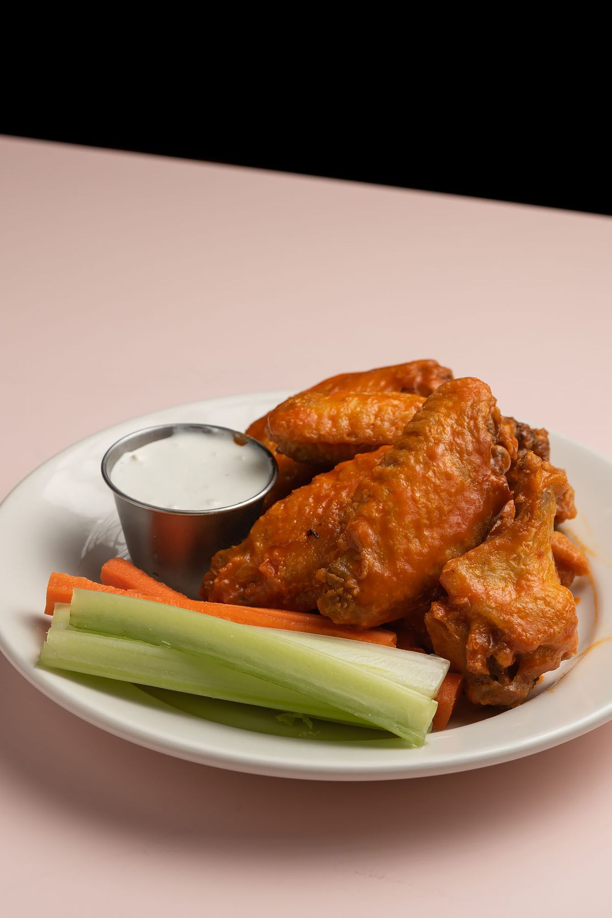 Chicken wings with vegetables on the side.