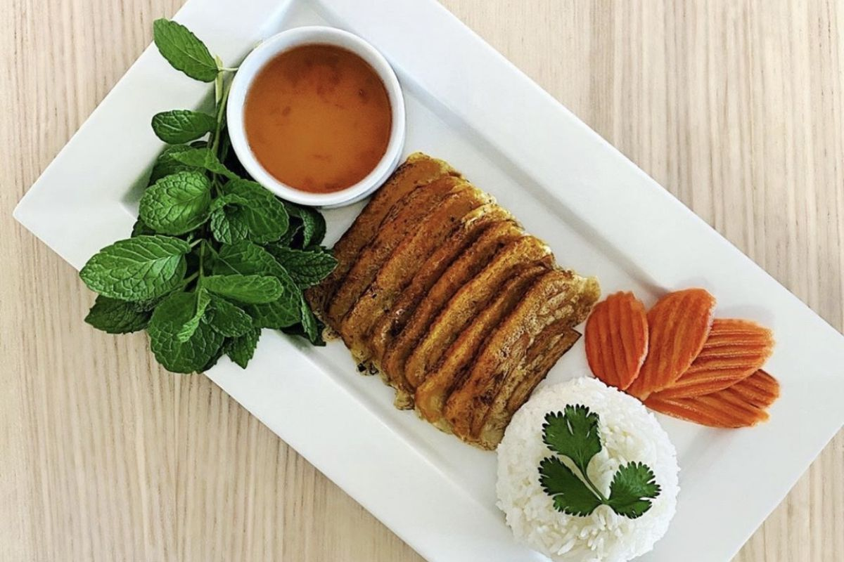 Seared tofu sits on a white plate next to a mound of rice and a cup of nước mắm chấm