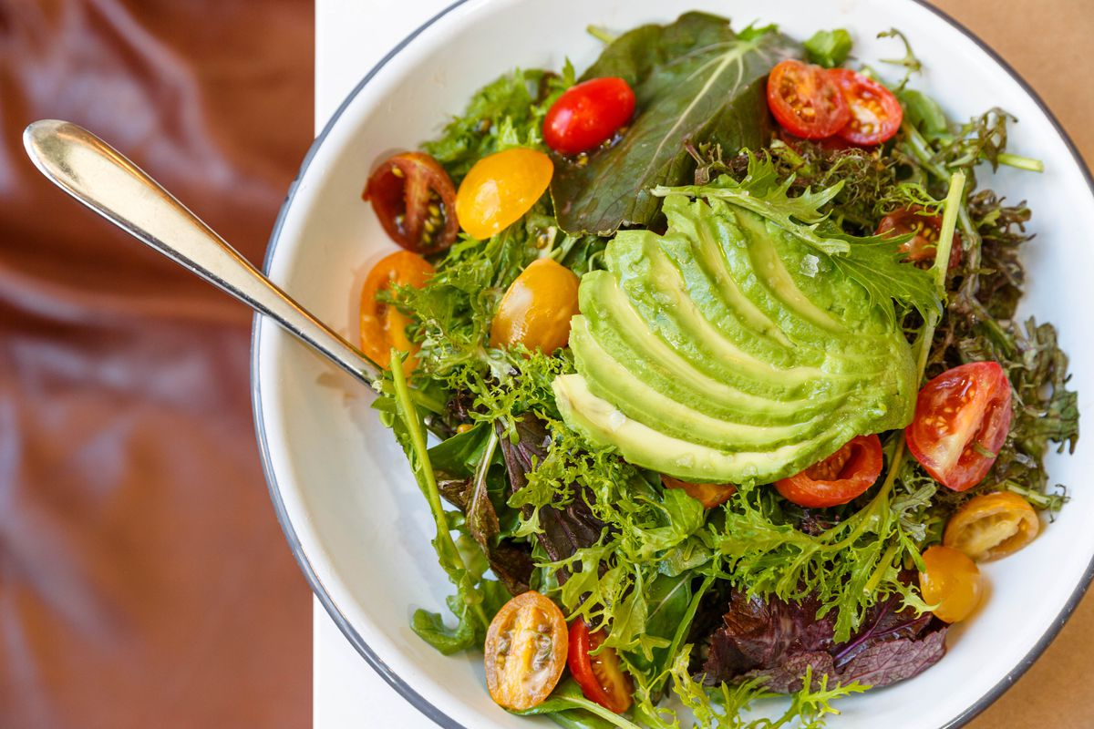 The shuk salad features avocado is a lemony dressing.