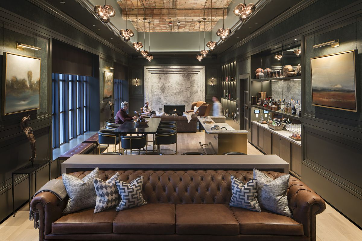 A room with dark walls, traditional moldings, exposed brick ceilings, dark brown sofas, and a bar.