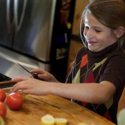 Sophia Udell, 7, cuts vegetables for a salad that was to be taken to Occupy Salt Lake demonstrators.