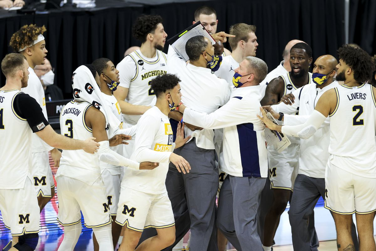 Michigan Wolverines head coach Juwan Howard (middle) is restrained by players and staff during a stop in play in the game against the Maryland Terrapins in the second half at Lucas Oil Stadium.